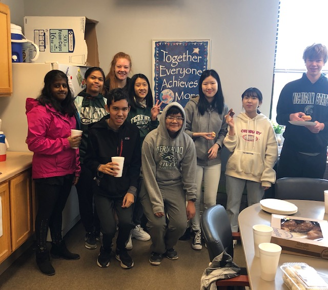 FHC students grabbing cider and donuts during a break from volunteering.
