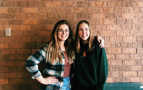 The new Table Toppers club ambassadors seniors Elle Ohlman and Dana Kistler pose in front of a brick wall.