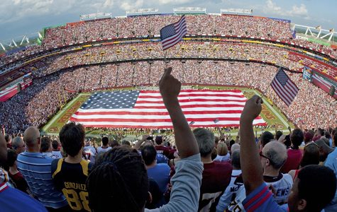 A giant American flag covers the field in honor of the 10th anniversary of 9/11 before an NFL football game between the New York Giants and the Washington Redskins, Sunday, Sept. 11, 2011, in Landover, Md. (AP Photo/Cliff Owen)