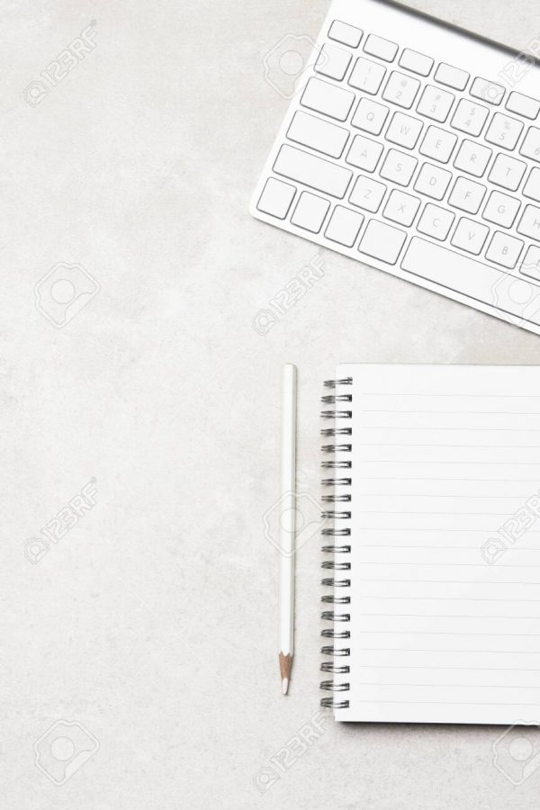 Vertical High Key Workspace: A note pad with white pencil and computer keyboard . Flat Lay, top view.