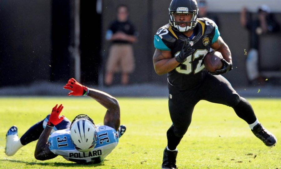 Dec 22, 2013; Jacksonville, FL, USA; Jacksonville Jaguars running back Maurice Jones-Drew (32) runs the ball past Tennessee Titans safety Bernard Pollard (31) during the game at EverBank Field. Mandatory Credit: Melina Vastola-USA TODAY Sports