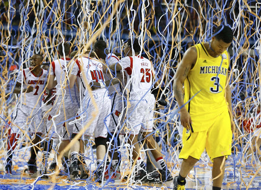 Michigan Wolverines guard Trey Burke (3) walks off the court as the Louisville Cardinals celebrate defeating Michigan to win the NCAA men