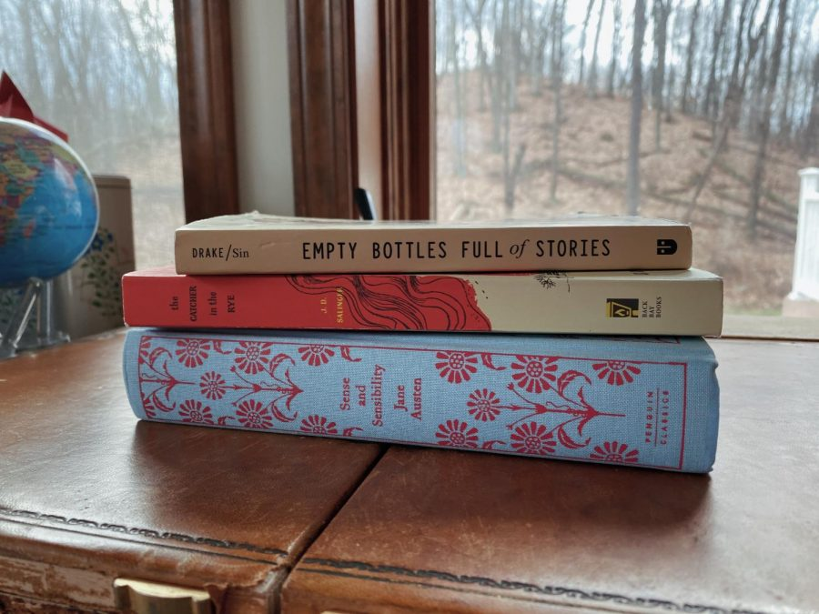 Three very different book genres piled on top of one another.