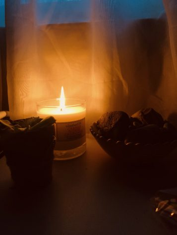a picture of my favorite candle sitting dangerously close to my curtains and my bowl of rocks.