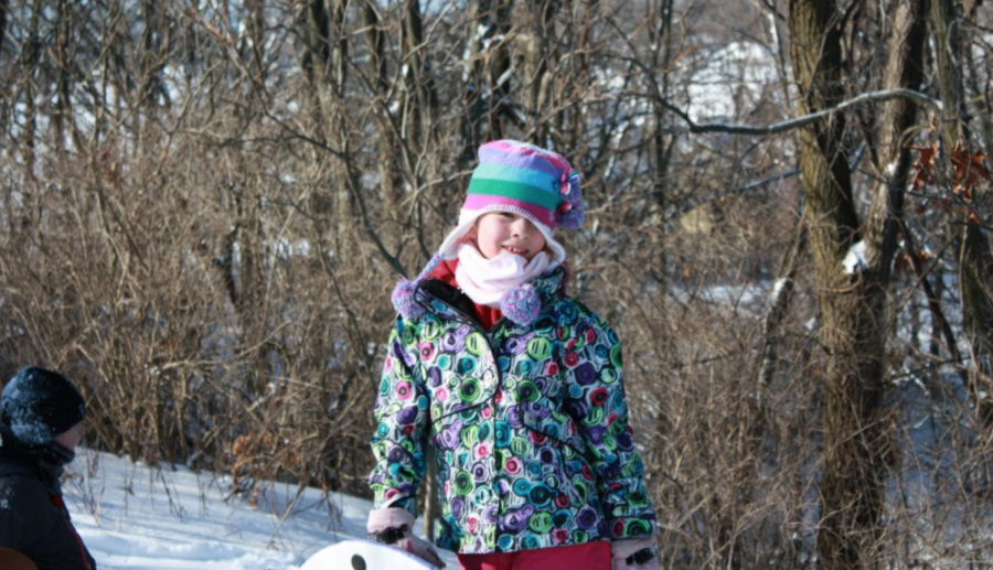 A photograph of me, bundled up and missing far too many teeth, ready to go sledding.