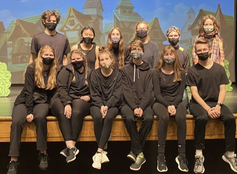 FHC's stage crew sitting on stage, wearing their masks, and posing for the camera after their most recent show