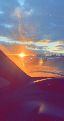 A peaceful drive as the sun sets ahead of the car.