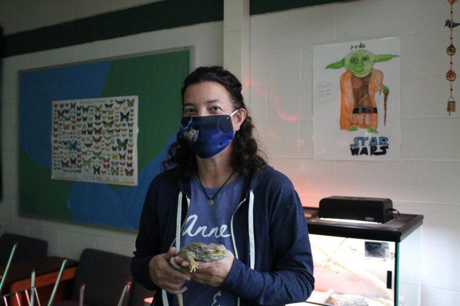 English teacher Dr. Keller, standing in her classroom, holding one of her pet lizards, Lamont
