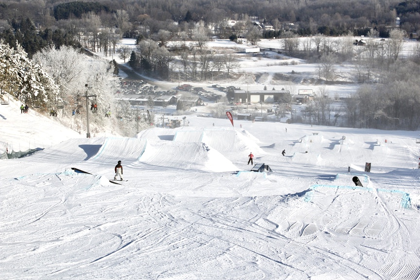 Snowboarders and skiers riding down a hill at Cannonsburg Ski Area.