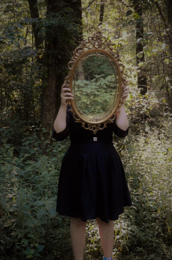 A girl standing in the woods, hiding her own reflection with the beauty of nature.