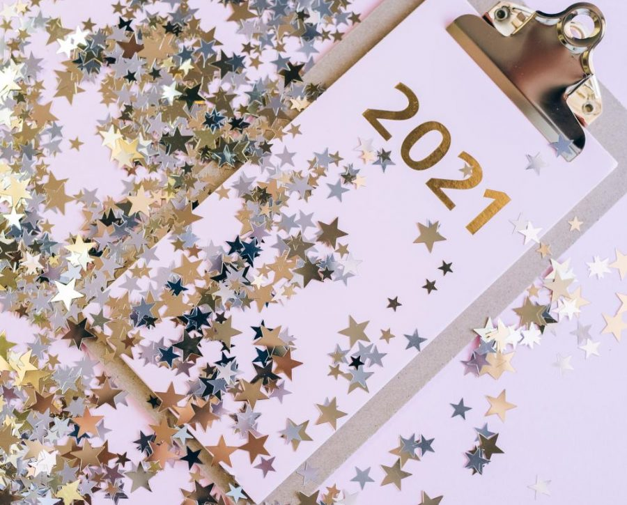 A clipboard labeled 2021 is covered with sparkling stars.