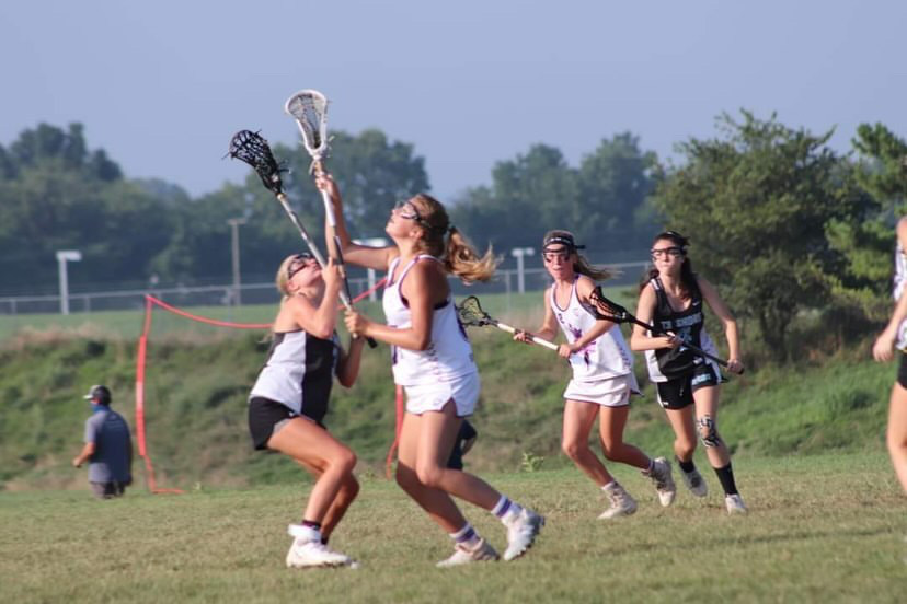 Maggie Sneider playing lacrosse, one of the three sports she participates in