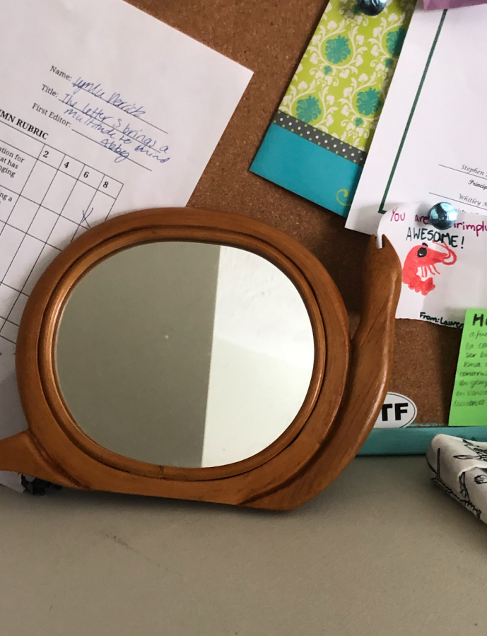 A picture of my snail mirror, a beloved 3 am purchase of mine, perched on a messy desk.