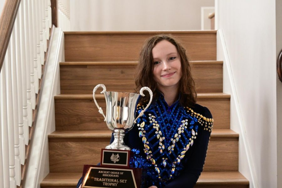 Penelope O'Meara posing with her dance trophy in her dance costume