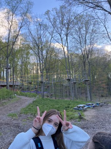 A picture of Nora in front of TreeRunner Adventure Park for her birthday.