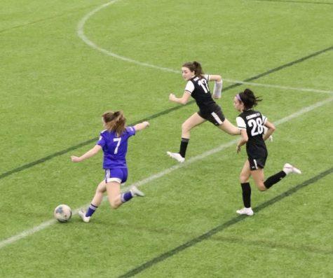 Number 7, Haley Ward, kicks the soccer ball.