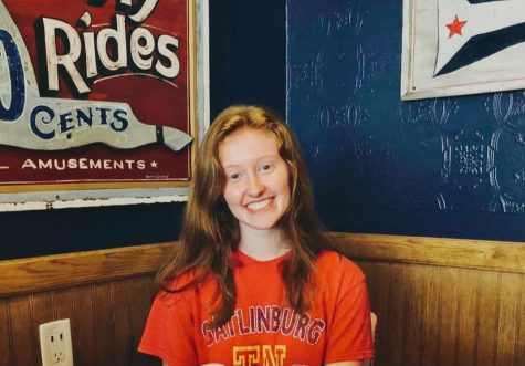 Freshman Kate Franklin sits, smiling against a blue wall, in the corner booth of a restaurant.