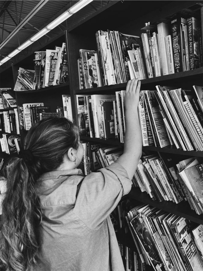 a picture of me in my dads old shirt reaching for books at the top of the shelf