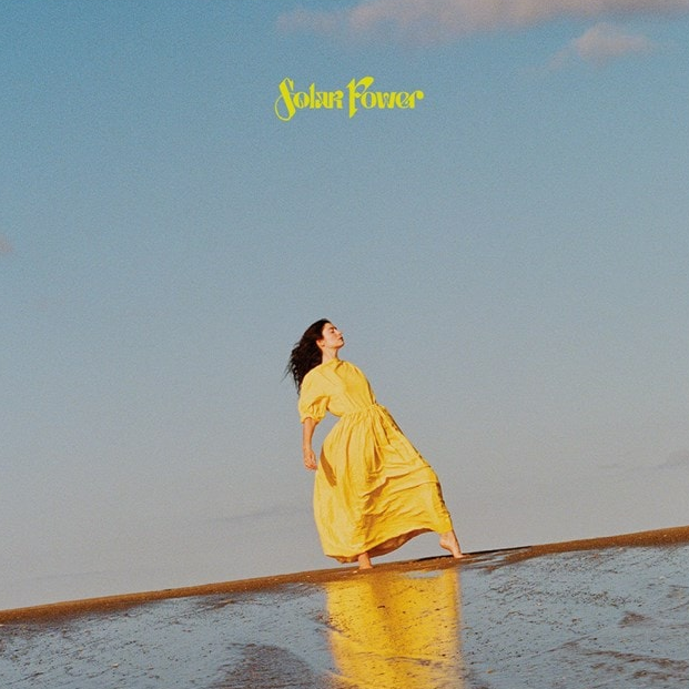 Here is one of the album covers for Solar Power featuring Lorde gracefully standing on a beach wearing a beautiful yellow gown.