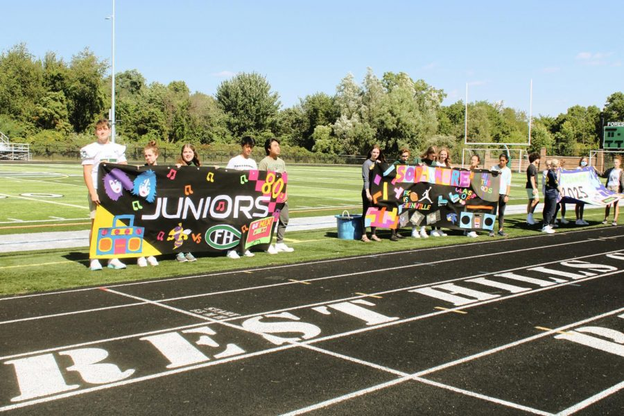 Each grade level proudly holds their hand-made banner