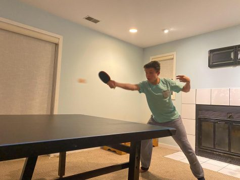 Logan Mix practices ping pong in his basement with his father.
