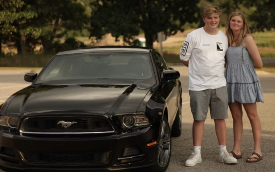 Madi and her brother, Nate, posing next to a car.