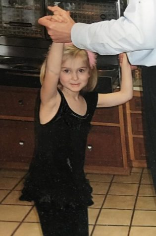 Young me dancing in the kitchen with my dad after putting on my favorite outfit.